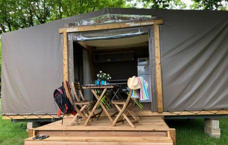 Terrasse en bois pour un apéro à l'ombre des arbres dans un camping